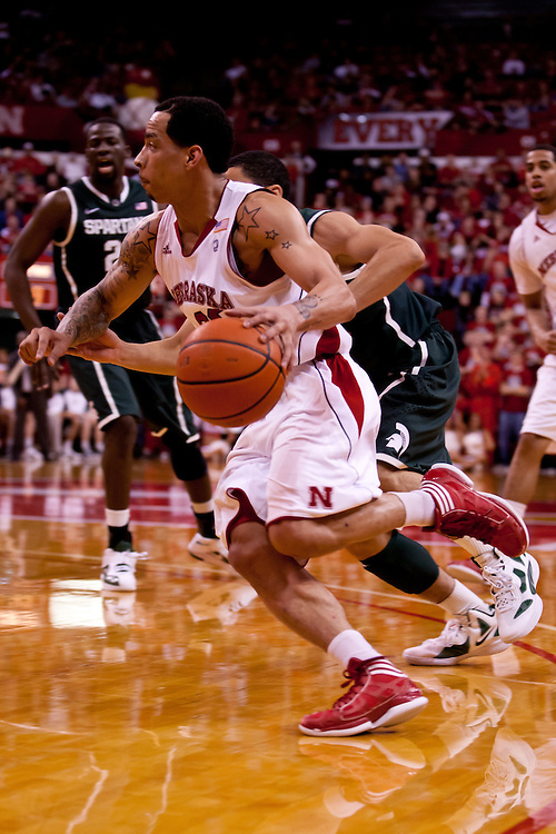 31 December 2011: Bo Spencer #23 of the Nebraska Cornhuskers drives to the basket against Keith Appling #11 of the Michigan State Spartans during the second half at the Devaney Sports Center in Lincoln, Nebraska. Michigan State defeated Nebraska 68 to 55.