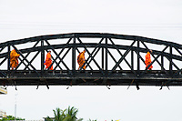 Buddhist monks cross the bridge over the river Kwai, Death Railway, Kanchanaburi, Thailand
