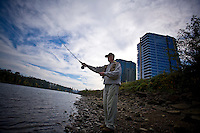 A man practices his fly fishing casting on the Willamette River. He is outside of his apartment on the South Waterfront in Portland, Oregon
