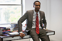 Portrait of happy African American businessman sitting on office desk