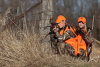 DEER HUNTERS WEARING BLAZE ORANGE SHOOTING A RIFLE WHILE GLASSING WITH BINOCULARS