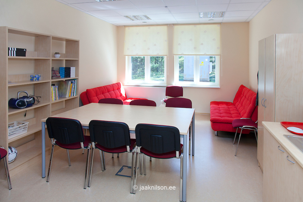 Staff room or teacher's rest room with  sofa and chairs in Metsapoole school, Estonia. Red covers. Table and upright chairs. Window. Shelves.