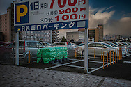 Irradiated topsoil removed during decontamination stored at a parking lot in central Fukushima City.