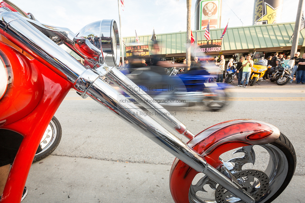 Bikers ride past a custom chopper along Main Street during the 74th Annual Daytona Bike Week March 8, 2015 in Daytona Beach, Florida. More than 500,000 bikers and spectators gather for the week long event, the largest motorcycle rally in America.
