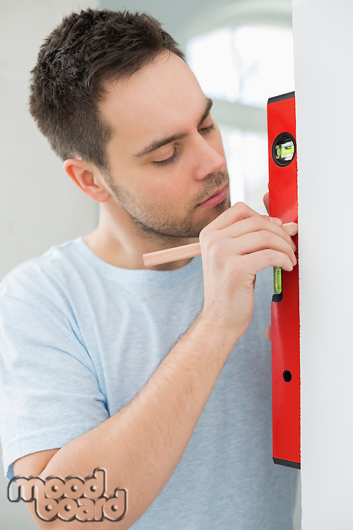 Mid-adult man marking on wall with level