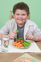 Overweight boy having healthy meal.