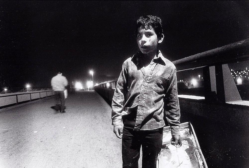 Young Churro vendor on bridge over Tijuana River.  1992