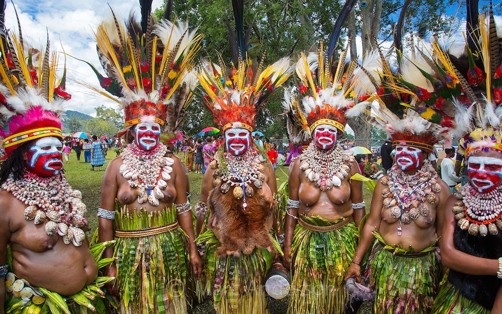 Colourful group of female dancers at the Goroka Show, Papua New Guinea. They are wearing large headdresses made from parrot's feathers and huge necklaces of seashells.