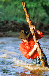 rugged cowboy in a stream fixing a fence