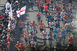 © Licensed to London News Pictures. 23/04/2017. LONDON, UK.  Mass marathon runners cross Tower Bridge, including a fancy dress knight with an England flag, seen from the glass walkway of Tower Bridge, as runners reach the half way point.  Photo credit: Vickie Flores/LNP