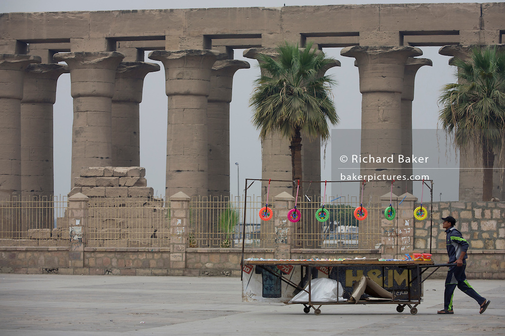A trinkets stallholder pushes his cart towards arriving tourists in front of the ancient Egyptian columns of Luxor Temple, Luxor, Nile Valley, Egypt. The temple behind was built by Amenhotep III, completed by Tutankhamun then added to by Rameses II. Towards the rear is a granite shrine dedicated to Alexander the Great and in another part, was a Roman encampment. The temple has been in almost continuous use as a place of worship right up to the present day.