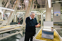 RUTIGLIANO, ITALY - 21 FEBRUARY 2018: Francesco Divella, CEO of Divella SpA, checks the penne candela (a type of pasta) before the packaging process at the Divella pasta factory in Rutigliano, Italy, on February 21st 2018.<br /> <br /> Opened in 1895, the plant just outside the regional capital of Bari is run by the grandson of the founder, Francesco Divella. Divella has exports grow substantially and is a prime example of the success of the region in recent years. Yet this has led to very few jobs, given that the plant is highly automated, with more on the way: they just bought a self-driving forklift to handle warehouse work and have already deployed robotic arms that place product into boxes. Divella is an example of how Italy's recent success is not lifting enough people to make a difference in sentiment.