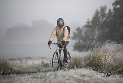 © Licensed to London News Pictures. 28/10/2019. London, UK. A woman cycles through a frost and mist covered landscape on a bright winter morning in Richmond Park, London. The UK is due to see brighter weather over the next few days, following days of heavy rain which caused flooding in parts. Photo credit: Ben Cawthra/LNP
