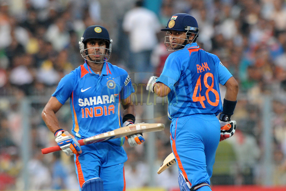 Suresh Raina of India and Manoj Tiwary of India run between the wickets during the 5th One Day International ( ODI ) match between India and England held at the Eden Gardens Stadium, Kolkata on the 23rd October 2011..Photo by Pal Pillai/BCCI/SPORTZPICS