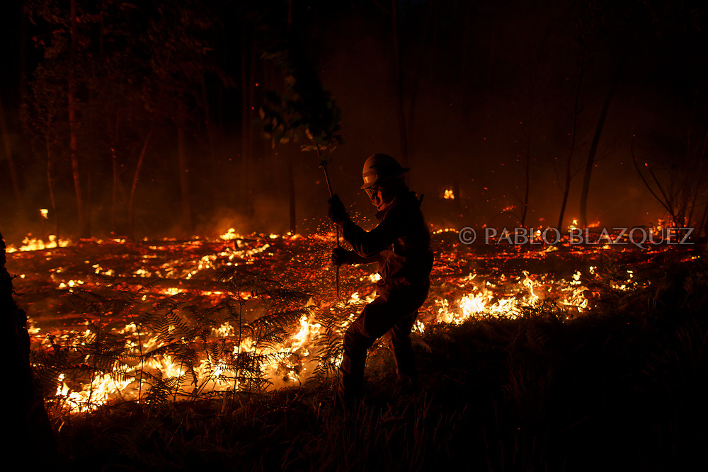 LEIRIA, PORTUGAL - JUNE 19:  A firefighter from the National Republican Guard GIPS tries to control a fire in the forest after a wildfire took dozens of lives on June 19, 2017 near Pedrogao Grande, in Leiria district, Portugal. On Saturday night, a forest fire became uncontrollable in the Leiria district, killing at least 62 people and leaving many injured. Some of the victims died inside their cars as they tried to flee the area.  (Photo by Pablo Blazquez Dominguez/Getty Images)