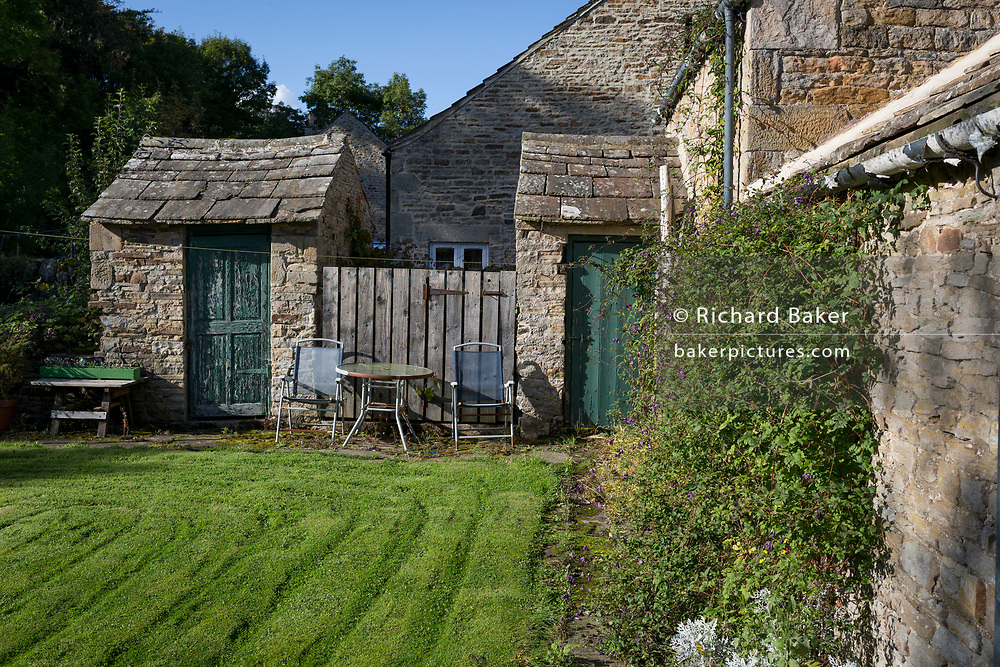 A rear garden landscape in the Northumbrian village of Blanchland, on 29th September 2017, in Blanchland, Northumberland, England. Blanchland is a village in Northumberland, England, on the County Durham boundary. The population of the Civil Parish at the 2011 census was 135. Blanchland was formed out of the medieval Blanchland Abbey property by Nathaniel Crew, 3rd Baron Crew, the Bishop of Durham, 1674-1722. It is a conservation village, largely built of stone from the remains of the 12th-century Abbey. It features picturesque houses, set against a backdrop of deep woods and open moors. Set beside the river in a wooded section of the Derwent valley, Blanchland is an attractive small village in the North Pennines Area of Outstanding Natural Beauty.