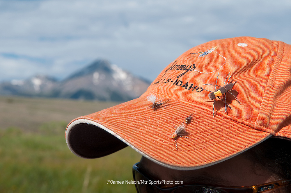 An 11-year-old boy with flies stuck in the bill of his ball cap while fly fishing on Birch Creek, Idaho.