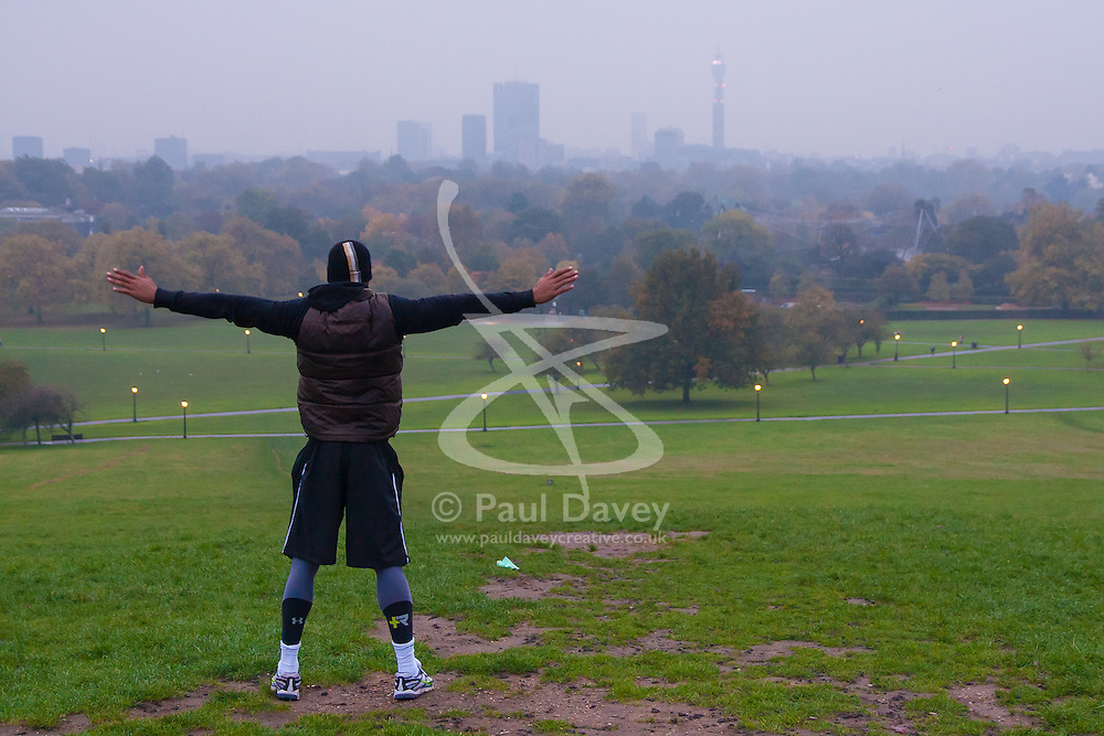 Primrose Hill, London, October 30th. As mist shrouds London's skline, fitness fanatics run and work out on Primrose Hill. Pictured: Ghanaian international footballer Junior Agogo exercises on Primrose Hill.