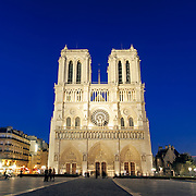 Photo of Notre Dame de Paris at night from directly in front, with the main, front facade illuminated and part of the square, with a deep blue sky.