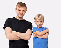 Portrait of happy father and son in casuals with arms crossed over white background