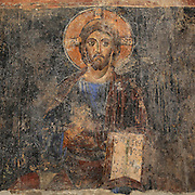 Fresco of Christ with crucifix halo and book, with hand raised in gesture of blessing, from the Church of Labova e Kryqit, or church of the Holy Cross, dedicated to St Mary, one of the oldest churches in Albania, mainly 13th century although with Byzantine foundations of 527-565 AD in the time of Emperor Justinian, Labova e Kryqit, Gjirokastra, Albania. The nave and aisle form a cruciform plan and the high central cupola is typically Byzantine. The interior walls are covered with 9 levels of frescoes. Picture by Manuel Cohen