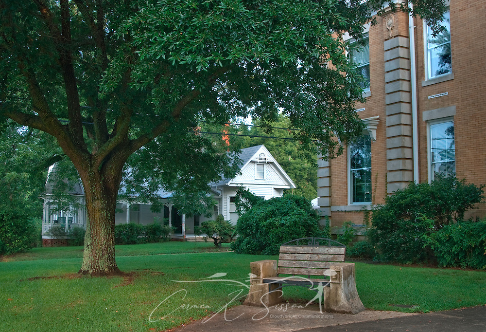 A wooden park bench offers a shady place for visitors to relax at the Hale County Courthouse in Greensboro, Alabama. (Photo by Carmen K. Sisson/Cloudybright)