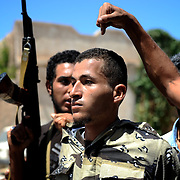 A pro-Gaddafi snipper is captured by a group of armed rebels near the frontline in eastern Zawiyah.