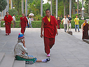 A monk wearing Crocs walks past a woman using a mobile 'phone, in the Sarnath Temple, near Varanasi, India