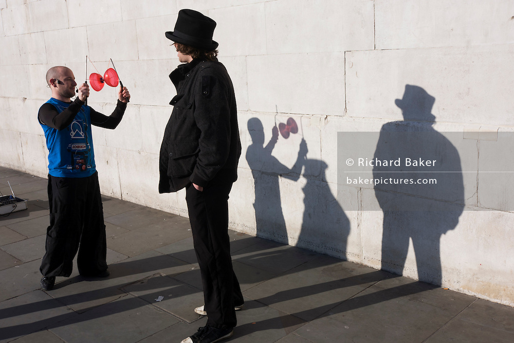 Two buskers are questioned by a police officer, their shadows played on a stone wall in Trafalgar Square.<br /> <br /> The diabolo (commonly misspelled as diablo; formerly also known as &quot;the devil on two sticks&quot;) is a juggling prop consisting of a spool which is whirled and tossed on a string tied to two sticks held one in each hand. A huge variety of tricks are possible using the sticks, string, and various body parts.