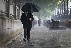 © Licensed to London News Pictures. 29/05/2018. London, UK. A man walks next to the River Thames just as thunderstorms bring heavy rain to the capital.  Photo credit: Peter Macdiarmid/LNP