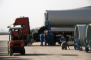Gansu, China - 25 Feb 2010. Workers load a truck with a wind turbine blade at Gansu Jinfeng Wind Power Equipment Co. Ltd. in Jiuquan, Gansu Province, China. China has set a target for renewable energy consumption of 40 percent of the market by the year 2050. Photographer: Markel Rendondo/Greenpeace.