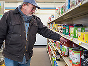 """25 FEBRUARY 2020 - BUTTERFIELD, MINNESOTA: KERMIT LEET, a retired teacher, looks at fruit juices in the grocery section of the True Value Hardware Store in Butterfield, MN, a farming community of about 500 people 130 miles southwest of the Twin Cities. The town has been a """"food desert"""" for 10 years after its only grocery store closed in 2010. Barb Mathistad Warner and Mark Warner purchased the True Value store in Butterfield in December, 2018 and started selling groceries in the store in May, 2019. For residents of Butterfield going to a grocery store meant driving 10 miles to St. James, MN, or 20 miles to Windom, MN, the two nearest communities with grocery stores. The USDA defines rural food deserts as having at least 500 people in a census tract living 10 miles from a large grocery store or supermarket. There is a convenience store in Butterfield, but it sells mostly heavily processed, unhealthy snack foods that are high in fat, sugar, and salt.   PHOTO BY JACK KURTZ"""