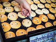 "06 FEBRUARY 2015 - BANGKOK, THAILAND: A worker at Thanusingha Bakery pulls traditional Thai Catholic desert cakes out of the baking pans. The cakes are called ""Kanom Farang Kudeejeen"" or ""Chinese Monk Candy."" The tradition of baking the cakes, about the size of a cupcake or muffin, started in Siam (now Thailand) in the 17th century AD when Portuguese Catholic priests accompanied Portuguese soldiers who assisted the Siamese in their wars with Burma. Several hundred Siamese (Thai) Buddhists converted to Catholicism and started baking the cakes. When the Siamese Empire in Ayutthaya was sacked by the Burmese the Portuguese and Thai Catholics fled to Thonburi, in what is now Bangkok. The Portuguese established a Catholic church near the new Siamese capital. Now just three families bake the cakes, using a recipe that is 400 years old and contains eggs, wheat flour, sugar, water and raisins. The same family has been baking the cakes at the Thanusingha Bakery, near Santa Cruz Church, for more than five generations. There are still a large number of Thai Catholics living in the neighborhood around the church.        PHOTO BY JACK KURTZ"