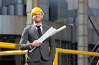 Portrait of smiling young male architect holding blueprints outside building