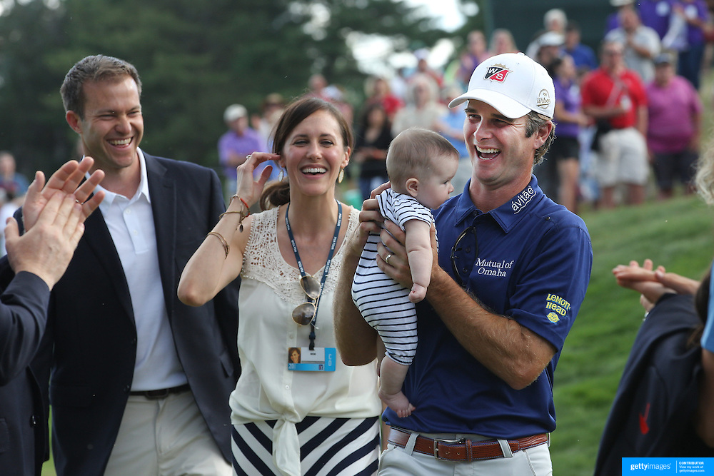 Kevin Streelman holding his 6-month-old daughter Sophia, watched by his wife Courtney after winning the Travelers Championship at the TPC River Highlands, Cromwell, Connecticut, USA. 22nd June 2014. Photo Tim Clayton