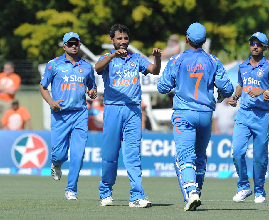India's Mohammed Shami, centre, celebrates with India's MS Dhoni after he took the catch off Shami's bowling to dismiss New Zealand's Ross Taylor for 55 in the first one day International cricket match, McLean Park, New Zealand, Sunday, January 19, 2014. Credit:SNPA / Ross Setford