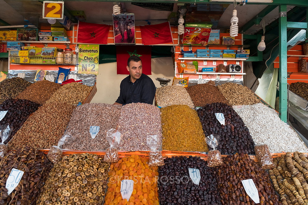 Vendor at a dried fruit and nut stand at Djemma el-Fna square in Marrakech, Morocco.