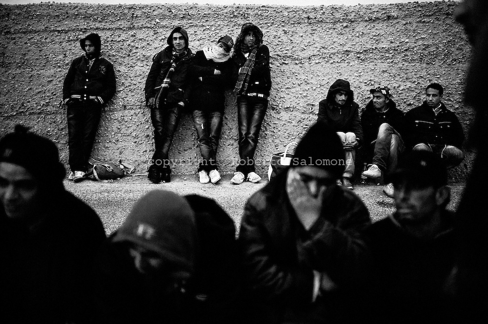 ITALY, Lampedusa : Immigrants who arrived during the night on the italian island of Lampedusa wait for a bus that will bring them to a temporary accomodation center on February 21, 2011. Italian Coast Guard said that the good weather conditions may increase the number of boats leaving from Tunisia to reach the shores of the italian island. AFP PHOTO / ROBERTO SALOMONE