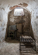 """Eastern State Penitentiary<br /><br />Eastern State Penitentiary was erected in 1929 and at the time, it was the largest and most expensive public structure in the country with a final price tag of $750,000. Its architectural significance first arose in 1821, when British architect John Haviland was chosen to design the building. Haviland found most of his inspiration for his plan for the penitentiary from prisons and asylums built beginning in the 1780s in England and Ireland. He gave the prison a neo-Gothic look to install fear into those who thought of committing a crime.<br />The """"Pennsylvania system"""" was implemented in Eastern State, a revolutionary system of incarceration which encouraged sepereate confinement as a form rehabilitation. Until 1904, prisoners entered the institution with a black hood over their head, so they would never know who their fellow convicts were, before being led to the cell where they would serve the remainder of their sentence in near-constant solitude. All contact with the outside world more or less ceased for Eastern State prisoners.<br />The basis design of the prison consisted of an octagonal center connected by corridors to seven radiating single-story cell blocks, each containing large single cells with hot water heating, a water tap, toilet and individual exercise yards the same width as the cell. But by the time cell block three was completed, the prison was already over capacity, so all cell blocks built thereafter consisted of two floors.<br />Each cell was lit by a single source of light either by a skylight or window, which was considered the """"Window of God"""" or """"Eye of God"""". The church viewed imprisonment, usually in isolation, as an instrument that would modify sinful or disruptive behavior. The time spent in prison would help inmates reflect on their crimes committed, giving them the mission for redemption.<br />Originally, inmates were housed in cells that could only be accessed by entering through a small exercise yar"""