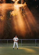 Sunlight streams through the trees behind an outfielder at Cronomer Hill Park in the Town of Newburgh, New York.