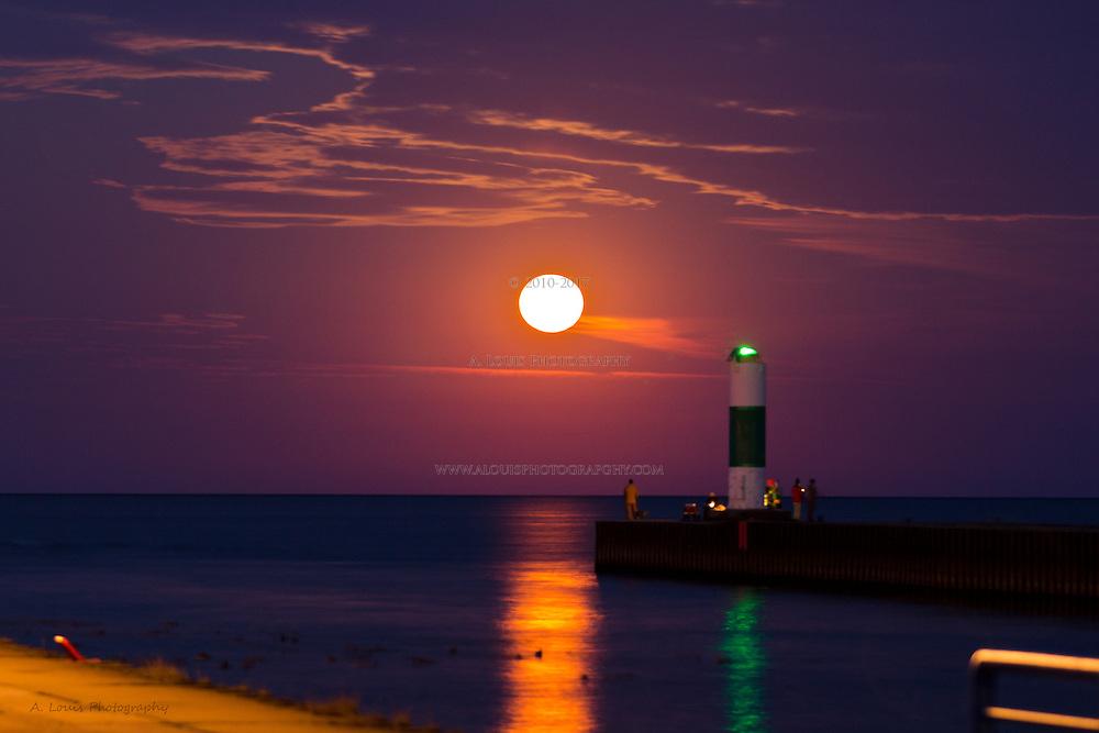 Full harvest moon setting on lake Michigan just minutes before sunrise