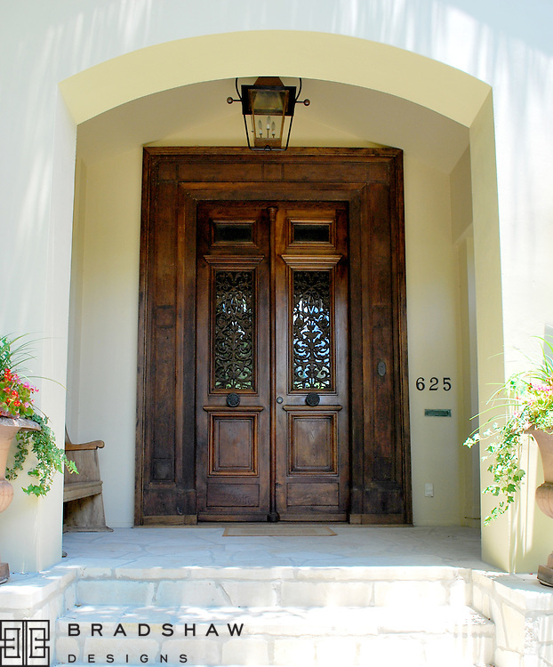 ANTIQUE FRENCH DOORS, LEUDERS STONE STAIRS AND LANDING, COPPER GAS LANTERNS AND RE-SHAPED ARCH RETURN SPANISH COLONIAL DETAILS TO A CHARMING HOUSE IN ALAMO HEIGHTS.