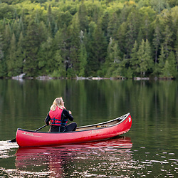 A woman paddles a canoe in Perch Pond in Aroostook County, Maine. Deboullie Public Reserve Land.