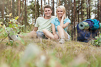 Full length of young hiking couple with backpack relaxing in forest