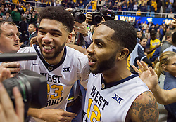 Jan 10, 2017; Morgantown, WV, USA; West Virginia Mountaineers forward Esa Ahmad (23) and West Virginia Mountaineers guard Tarik Phillip (12) celebrate with fans after beating the Baylor Bears at WVU Coliseum. Mandatory Credit: Ben Queen-USA TODAY Sports