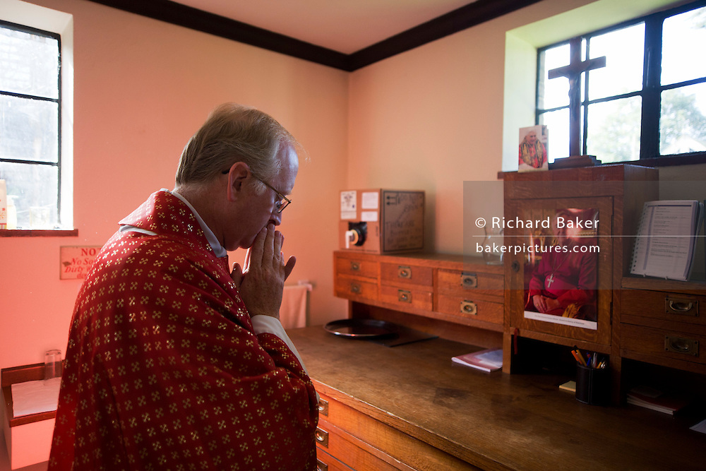 Priest says brief prayer in backroom Sacristy (Vestry) before Mass at St. Lawrence's Catholic church in Feltham, London.