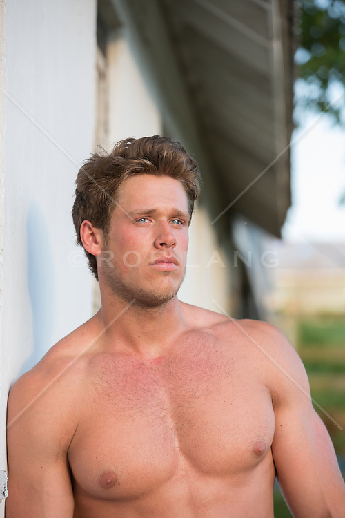 All American man without a shirt leaning against a barn
