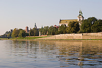 late afternoon sunshine falls on pauline church and the river vistula seen from the opposite bank.