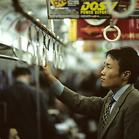 Japan, Tokyo, Young adult businessman standing aboard crowded downtown subway train during evening commute