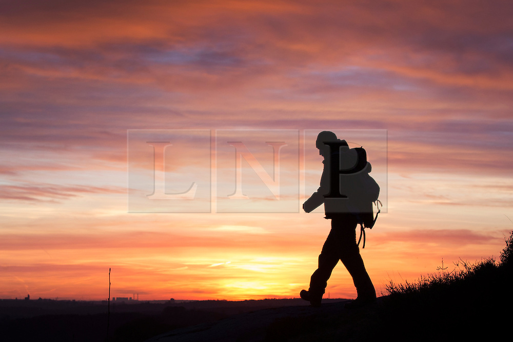 © Licensed to London News Pictures. 25/01/2016. Baildon UK. A man takes an early morning walk in this mornings sunrise on Baildon Moor as Britain braces itself for more bad weather as fears grow that Storm Jonas will hit Britain. Photo credit: Andrew McCaren/LNP